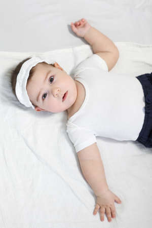 Calm baby boy lying on his back, dressed white t-shirt and bandage