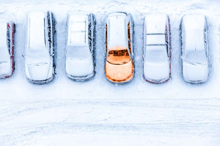 Top view at line from parked cars with one unit warmed up, pre-heating system at winter season