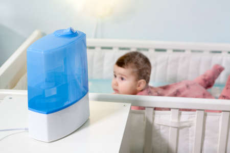 Baby girl lying on stomach in crib with humidifier in use. Respiratory disease prevention at home