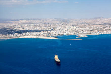 Aerial view at Larnaca city and Main Harbor in Cyprus island. Dry-cargo freighter coming from port