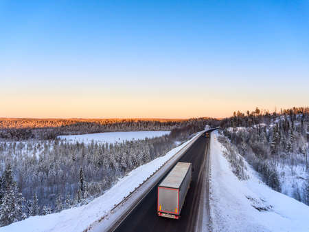 Truck moving on the Kola highway, aerial view at northern road with vehicles at polar night. Karelia, Russia