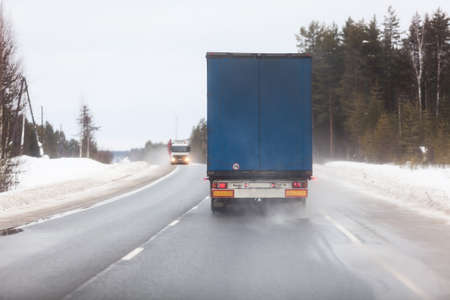 Rear view at semitrailer truck driving on slippery winter road in northern forests Foto de archivo - 139862165