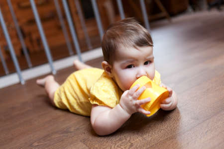 Baby child nibbling plastic block of pyramid, teething problems. Domestic room with hardwood floor