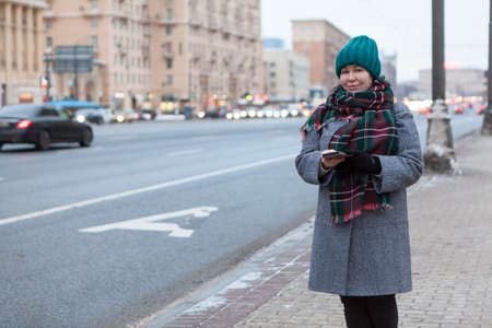 Young woman dressed warm coat, scarf and hat standing roadside, waiting taxi or public transport