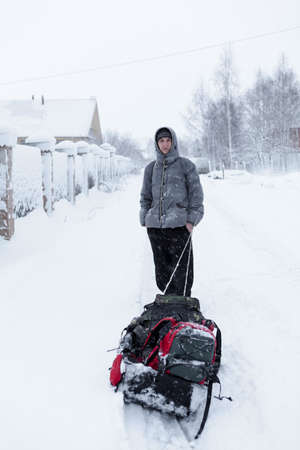 Adult Caucasian man portrait standing with drag sled in the snowy village during strong snowfall Фото со стока