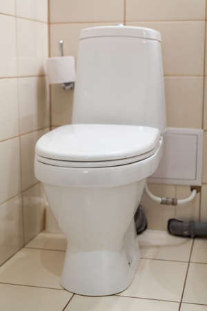 Clean white bathroom toilet with the lid closed, front view