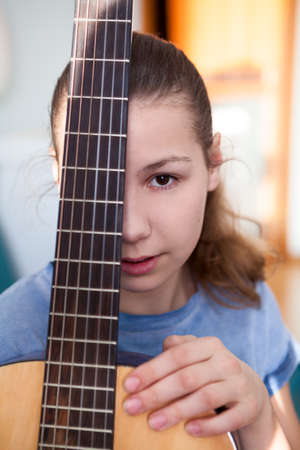 Portrait of teenage girl guitarist with fretboard of guitar, looking at camera
