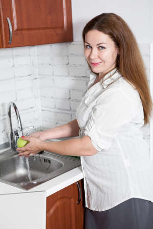 Cheerful Caucasian woman washes green apple in sink in domestic kitchen, smiling housewife 免版税图像