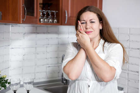 Young woman with toothache standing in kitchen, holding her cheek with hands