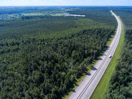 Wide straight toll highway M-11passing in forests. View from above. The Moscow-Saint Petersburg motorway designed as the ?11 Neva is in Russia