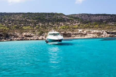 Blue lagoon of Mediterranean sea with luxury speedboat on water surface. Cyprus island with beautiful coastline