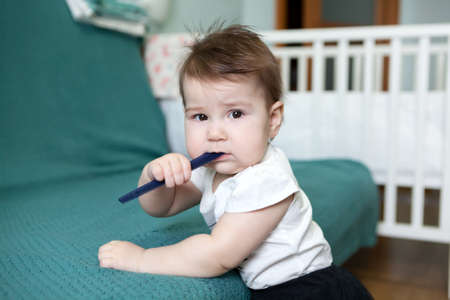 Baby girl is chewing plastic hairbrush while teething, Caucasian child is in domestic room