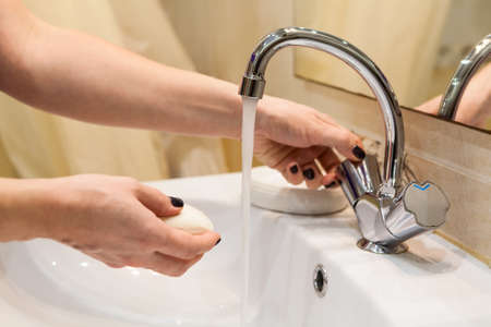 Person starting washing hands, opening water tap with soap in other hand