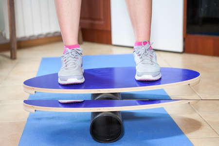 Balance board, close up view with athlete feet, rubber mat.