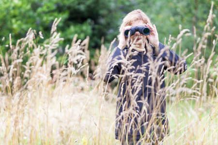 Woman ornithologist studying birds with binoculars, vanished out of sight in high grass