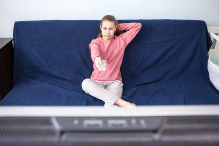 Pre-teen age girl watching television, sits on couch with tv remote control, wide screen is on a foreground