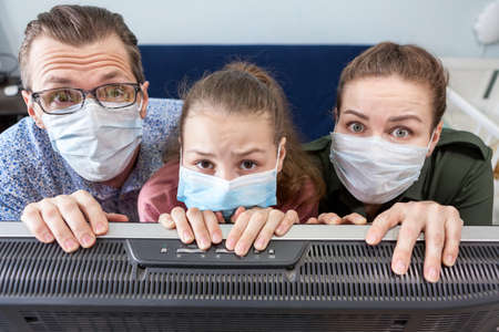 Caucasian father, mother and teenage girl wearing medical masks, standing close to tv set, weary of prolonged idleness