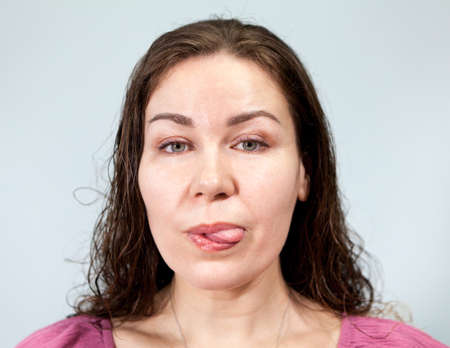 Woman with long hair showing tongue and looking at camera, portrait on grey background, emotions series.
