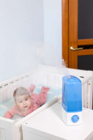 Using ultrasonic air humidifier for prevent pulmonary disease, Caucasian infant child lying in bed in a domestic room