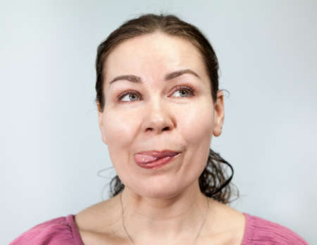 Woman flirty shows tongue and looks away, portrait on grey background, emotions series.