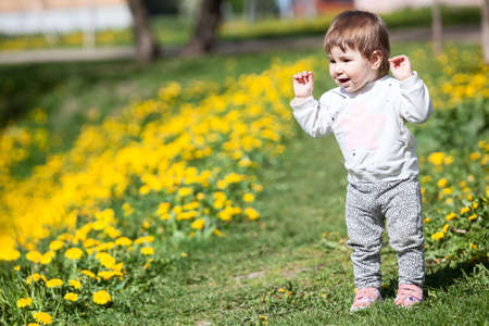 Happy laughing little child with hands up, walks and rejoicing to step his legs himself