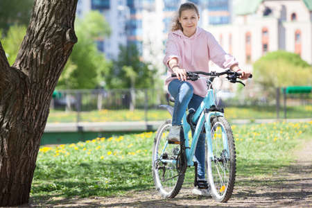 Smiling happy Caucasian teen age girl riding modern bicycle on city park, looking at camera