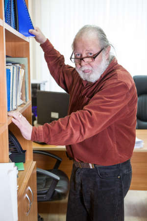 Senior bearded man puts documents into a shelf in office. Brown shirt and eyeglasses