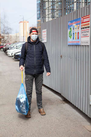 Adult man taking out garbage during the coronavirus pandemic, it is allowed without any permission. Inscription on plate in Russian: trush enclosure and attention videosurveillance