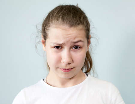 Confusion, misunderstanding on the face of a teenage girl, background, emotions series.