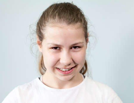 The grinning pre-teen girl looks at the camera, grey background, emotions series.