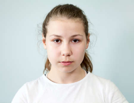 Young Caucasian girl with a neutral expression on her face. Portrait on grey background, emotions series.