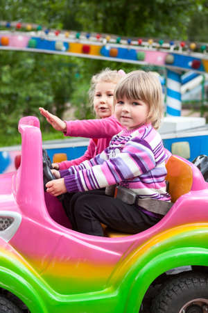 Two happy Caucasian little girls having fun in outdoor amusement park with riding in car on carousel, driving with steering wheel Standard-Bild