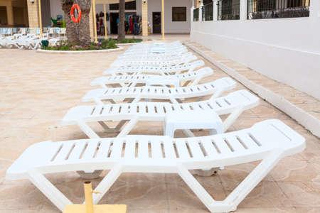 Empty white plastic sunbeds are on terrace of a hotel area, cancelled resort season via coronavirus