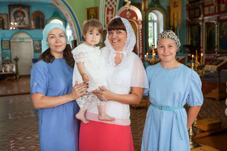 Mother with toddler and teenage daughters standing in church, godmother holding her goddaughter in arms