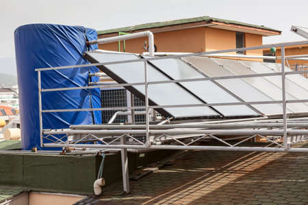 Solar glass water panel array mounted on a roof for heating. Huge tank for hot water