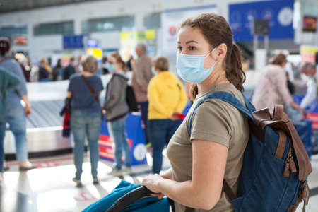 Woman traveller wearing medical mask waiting her suits and bags in luggage claim area in an international airport 版權商用圖片