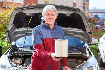 Senior driver holding new clean air cartridge for engine airbox. Car with opened hood is on a background Фото со стока
