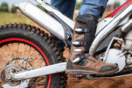 Close-up view at rider's motocross boot standing on peg of dirt motorcycle. Safety apparel for riding