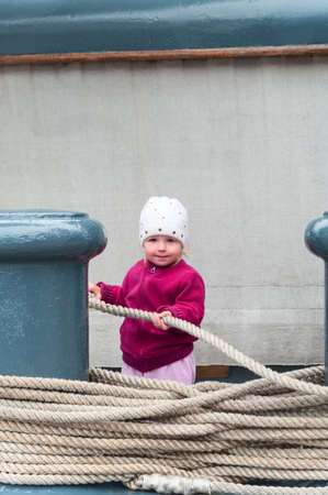 Smiling and happy Caucasian girl playing and holding on to the rope, looking at a camera 免版税图像