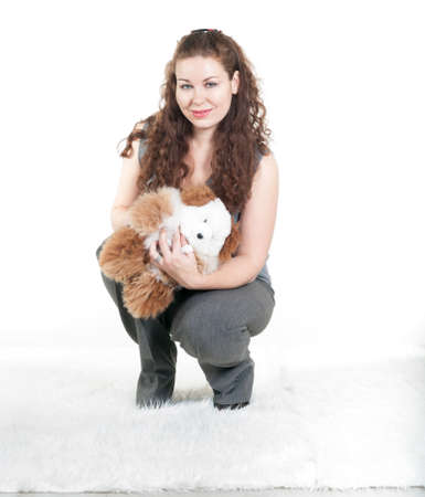 Curly hair woman holding teddy bear in hands, white background, a studio shot