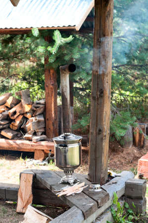 Smoking Russian samovar, metal boiling tank with pipe as a chimney for burning fire logs, vertical image