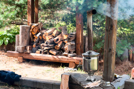 Smoking Russian samovar, metal boiling tank with pipe as chimney for burning fire logs, the horizontal image