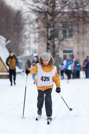 Young Caucasian girl running cross-country ski at a competition, winter activities