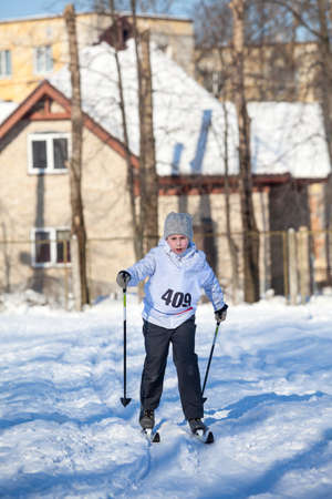 Young Caucasian girl running cross-country ski at a sport competition, winter activities 免版税图像