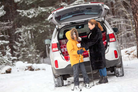 Mother dress a child for skiing while standing close to opened back door of car, cold weather in winter season