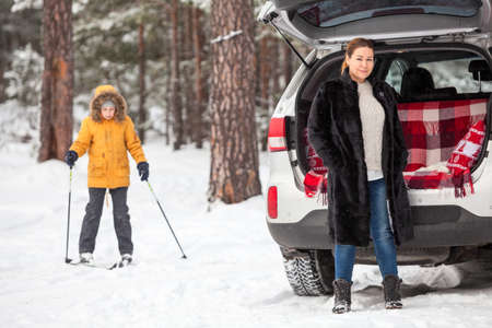 Mother waiting her daughter close to car until girl riding on ski in forest, winter activities