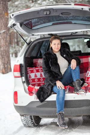 Woman wearing black fur coat sitting in her suv with opened back door, walking in forest at winter season