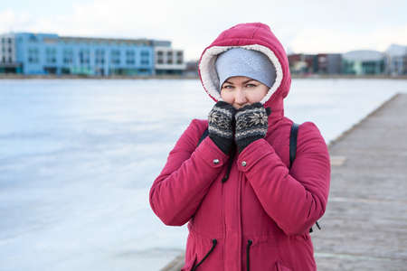 Adult woman wearing warm coat with hood on head and knit mittens standing on quay of a frozen lake 免版税图像