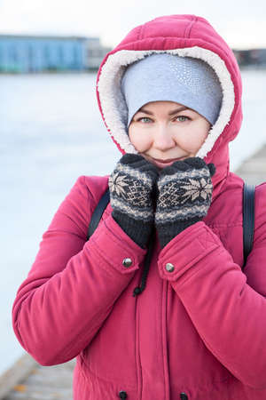 Portrait of an adult Caucasian woman dressed warm red jacket with hood on her head and knit mittens standing on quay of a frozen lake 免版税图像