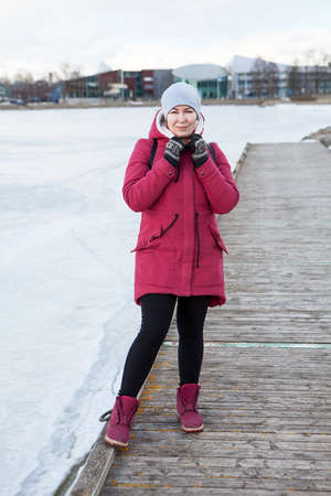 Full length portrait of an adult woman wearing warm coat with hood on head and knit mittens standing on quay of a frozen lake